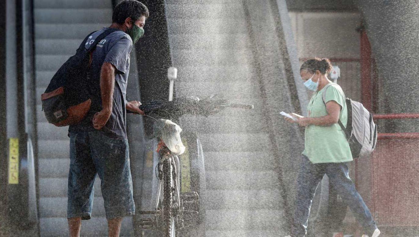 Osoby dojeżdżające do pracy przechodzą przez kabinę dezynfekującą wchodząc na stację metra w centrum Osasco, w Sao Paulo (fot. PAP/EPA/Sebastiao Moreira)