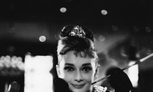 """Moda na papierosy na dobre eksplodowała po II wojnie światowej i od lat 50. łatwiejsze już było stworzenie listy gwiazd, których na srebrnym ekranie nie widziano z dymskiem niż tych, którzy palili. Tak jak Audrey Hepburn (1929 - 1993) m.in. w roli uroczej poszukiwaczki złota Holly Golightly w """"Śniadaniu u Tiffany'ego"""" (1961) w reżyserii Blake'a Edwardsa. Fot. via John Kobal Foundation/Getty Images"""