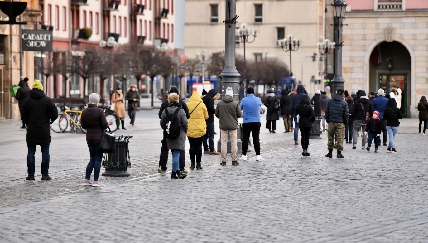 Osoby oczekujące w kolejce do całodobowego urzędu pocztowego (fot. PAP/Maciej Kulczyński)