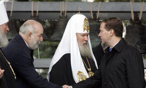12 września 2008 r. Ówczesny prezydent Rosji Dmitrij Miedwiediew wita się z rosyjskim potentatem naftowym Wiktorem Wekselbergiem (z lewej) podczas ceremonii poświęcenia 18 dzwonów w klasztorze Daniłowskiego w Moskwie. W środku – prawosławny patriarcha Rosji Aleksiej. Oryginalne wielowiekowe dzwony zostały sprzedane za granicę przez rząd sowiecki za rządów Józefa Stalina. Teraz dzowny zostały zwrócone Rosju przez amerykański Uniwersytet Harwarda w zamian za ich kopie. Fot. REUTERS / Alexander Natruskin