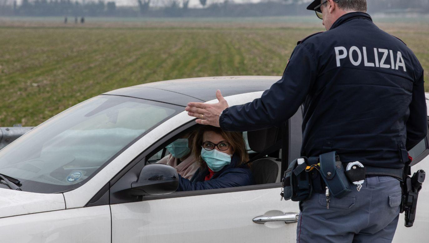 Włoski policjant instruujący kierowcę przed wjazdem do rejonu objętego kwarantanną (fot. Emanuele Cremaschi/Getty Images)