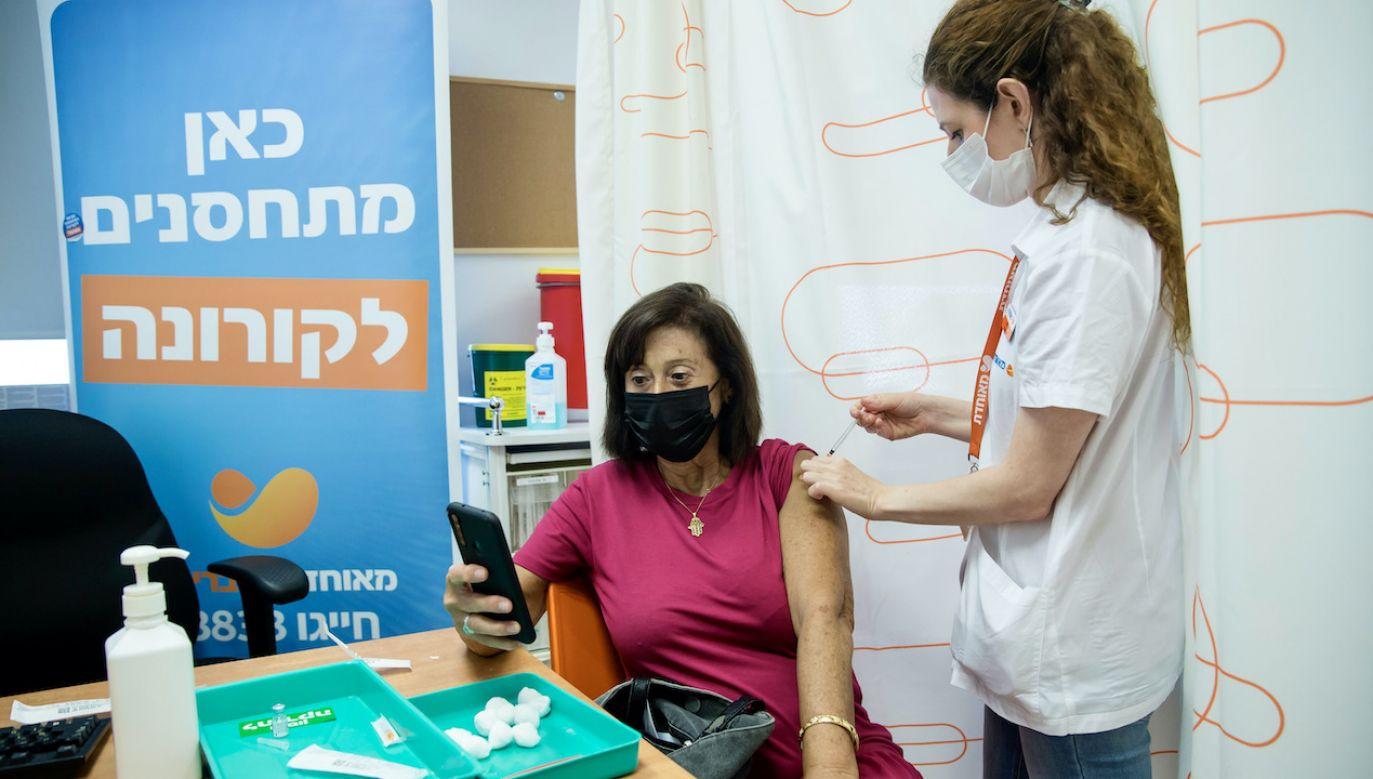 Pacjentka robi zdjęcie, w trakcie szczepienia trzecią dawką szczepionki COVID 19 (fot. Amir Levy/Getty Images)