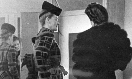 """Hebda radziła paniom na łamach wielkanocnego """"Nowego Kuriera Warszawskiego"""" z 1944 roku: """"Najwięcej spotykanym surowcem obecnych czasów są dwie lub trzy sukienki, z których szyjemy jedną, łączoną z tamtych trzech. Dlatego spotykamy tyle sukien z karczkiem bądź łączonych z dwóch lub trzech kolorów. Także na płaszcz nadaje się męski wełniany szlafrok"""". Tu: kobiety przymierzają eleganckie płaszcze. Fot. NAC/Jerzy Łuczyński, Wydawnictwo Prasowe Kraków-Warszawa, sygnatura: 2-7139"""