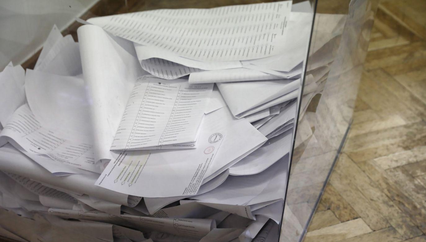 Jeden z wyborców wrzucił do urny kartę z kandydatami do Sejmu, wyniósł z lokalu drugą, z nazwiskami kandydatów do Senatu (PAP/Tomasz Gzell)
