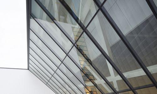 Ściana z jednej strony ostro ścięta, jakby odrąbana i przysłonięta szklaną taflą. Fot. Studio-Libeskind/©HuftonCrow